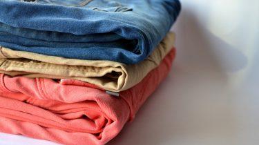 pilha de três calças coloridas como tirar cola de roupa